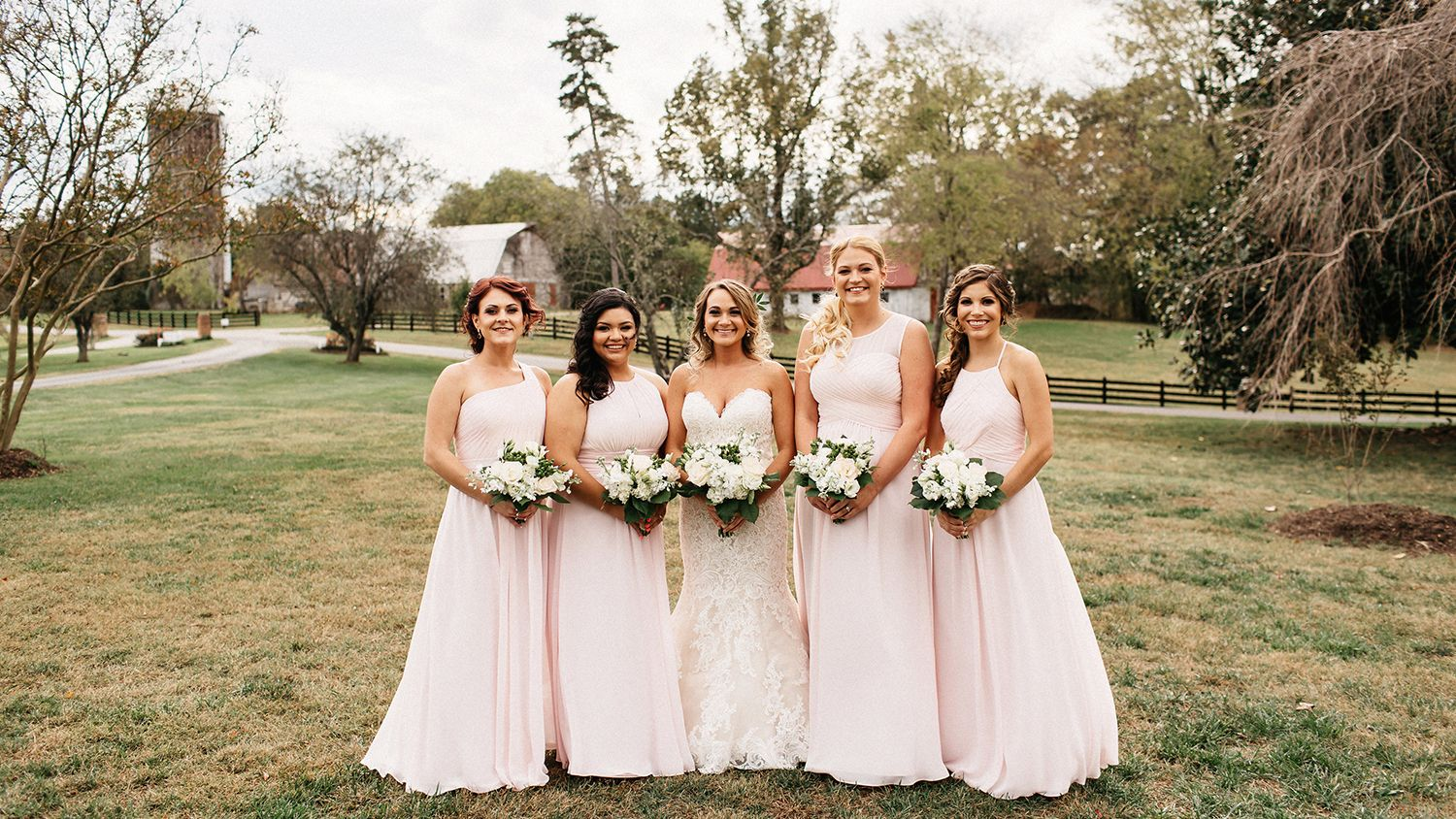 Bride and Bridesmaids Field in Front of Farmhouse facing Dairy Barn