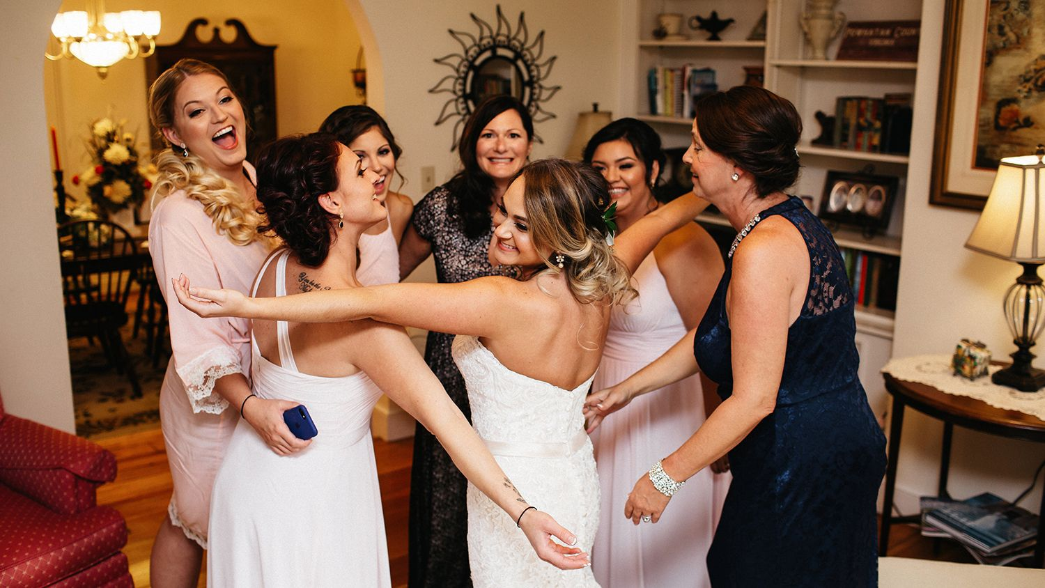 Bridal Party And Mother Hugging Farm House