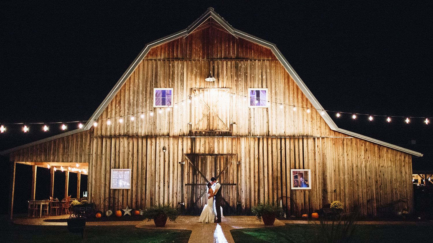 Bride And Groom In Front Of Reception Barn Night Lights