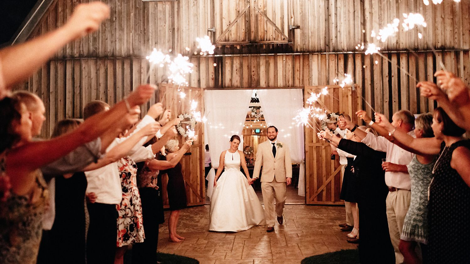 Bride And Groom Evening Sparkler Exit in front of Barn