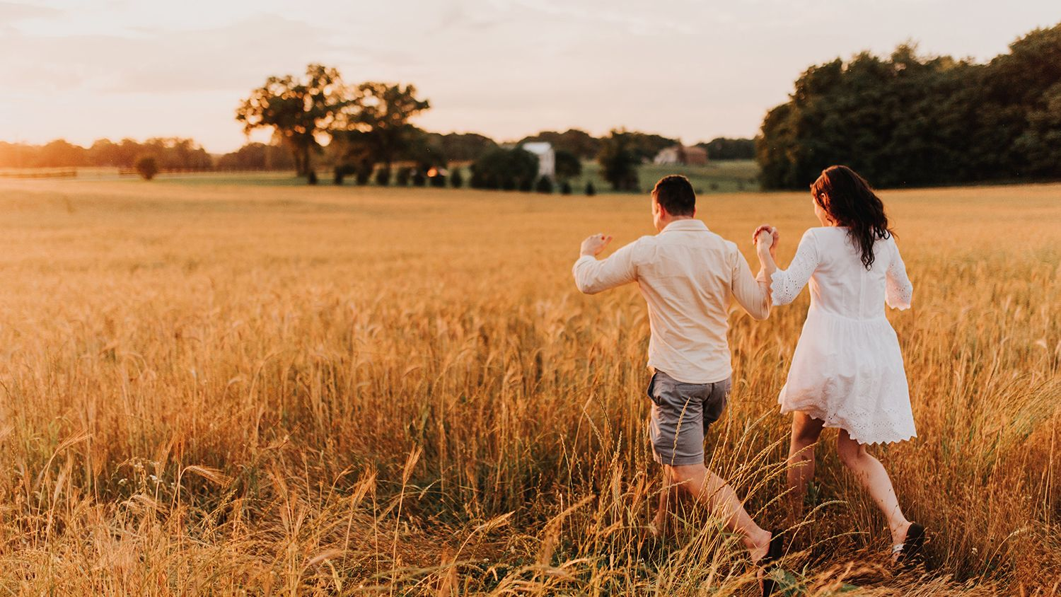 Bride And Groom Running Through Farm Field Sunset