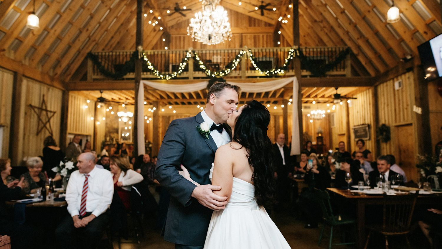 Bride And Groom Kissing In Reception Barn