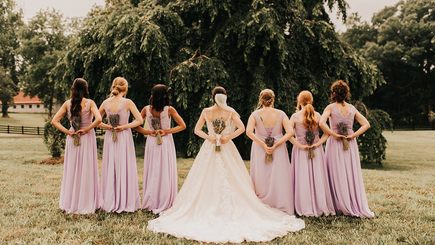 Bride With Bridesmaids Holding Flowers Field