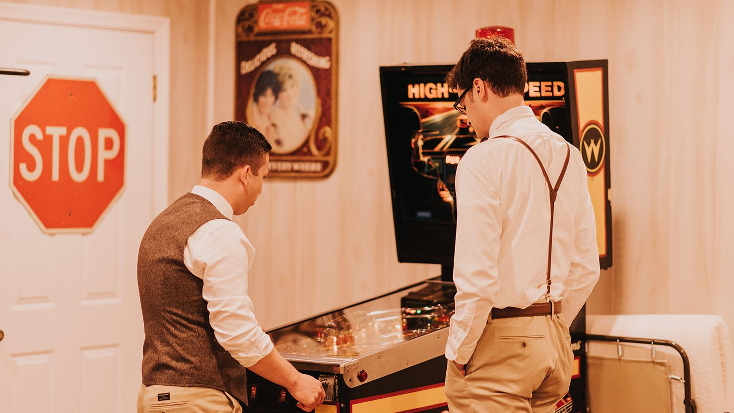 Groom Playing Pinball in Game Room