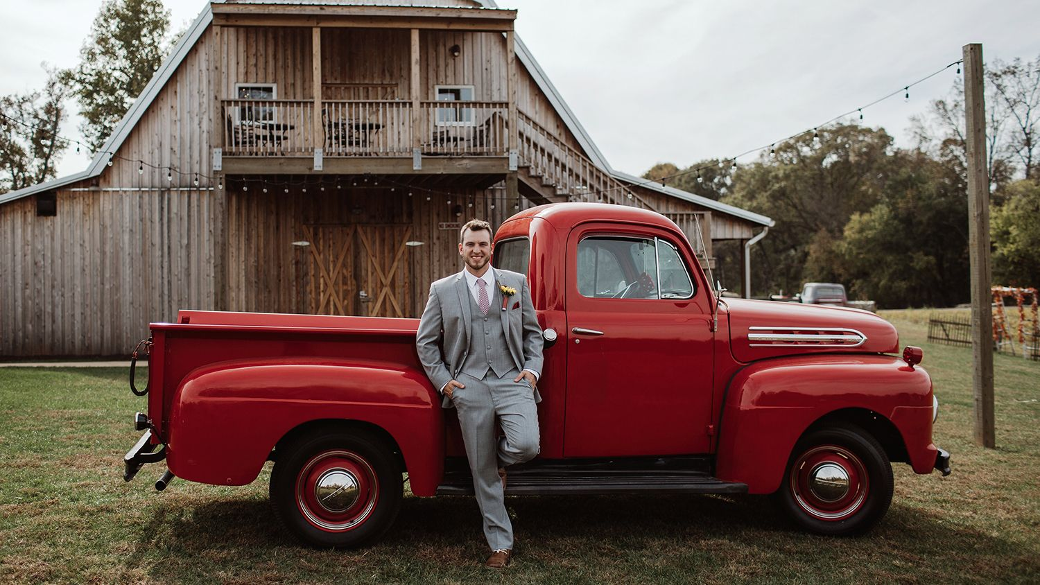 Groom Red Pickup Truck in Front of Reception Barn