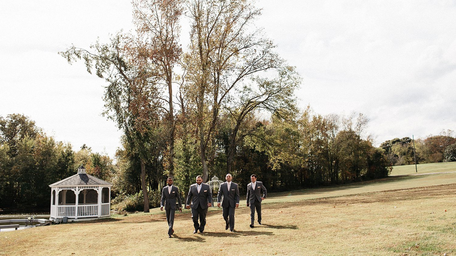 Groomsmen Walking Through Field Near Gazebo